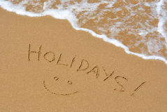 Holidays, handwriting on the beach sand Stock Photo