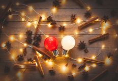 Holidays illuminations and bulbs. Cinnamon with star anise around on wooden background. Image in old color style Stock Photos