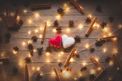 Holidays illuminations and heart shape toy. With cinnamon and star anise around on wooden background. Image in old color style Royalty Free Stock Images