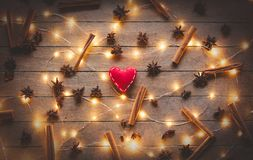 Holidays illuminations and heart shape toy. With cinnamon and star anise around on wooden background. Image in old color style Royalty Free Stock Photo