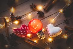 Holidays illuminations and heart shape toys. With cinnamon and star anise around on wooden background. Image in old color style Royalty Free Stock Photos