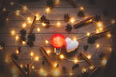Holidays illuminations and heart shape toys. With cinnamon and star anise around on wooden background. Image in old color style Stock Image