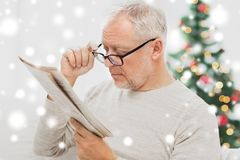 Senior man in glasses reading newspaper at home Stock Images