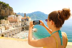 Holidays in Italy! Beautiful young woman take picture with smart phone of Atrani village on Amalfi Coast, Italy stock image