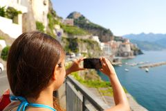 Holidays in Italy! Beautiful young woman take picture with smart. Phone of Atrani village on Amalfi Coast, Italy royalty free stock images