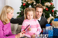 Holidays: Little Girl Lighting Candles for Hanukkah. A young mixed-religion family celebrating Hanukkah and Christmas, with presents, a menorah, Christmas tree