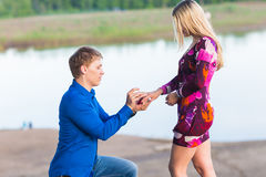 Holidays, love, couple, relationship and dating concept - romantic man proposing to a woman on nature Royalty Free Stock Photo