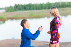 Holidays, love, couple, relationship and dating concept - romantic man proposing to a woman on nature Stock Photos