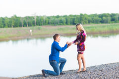 Holidays, love, couple, relationship and dating concept - romantic man proposing to a woman on nature Stock Image