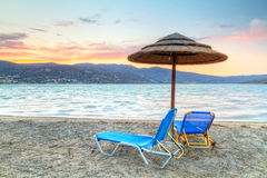 Holidays at Mirabello Bay in Crete. Deckchairs with parasol at Mirabello Bay at sunset, Greece Stock Photos