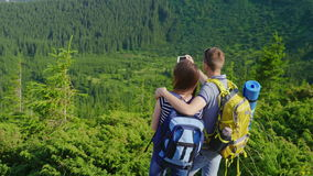 A young couple is photographed in a picturesque mset on the background of the mountains covered with forest. Holidays in the mountains in the summer. A man stock video footage