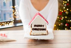 Close up of woman with christmas gingerbread house. Holidays, pastry and bakery concept - close up of woman holding and showing gingerbread house at home over royalty free stock image