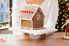 Close up of woman with christmas gingerbread house. Holidays, pastry and bakery concept - close up of woman holding and showing gingerbread house at home over stock photos