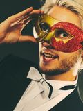 Young man in carnival mask on dark Stock Photo