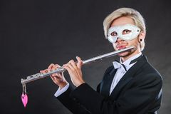 Man in carnival mask playing flute Royalty Free Stock Photo