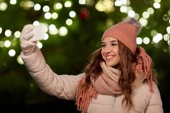 Young woman taking selfie over christmas tree Royalty Free Stock Images