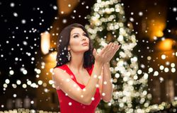 Beautiful woman in red dress over christmas tree Royalty Free Stock Photography