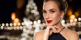 Beautiful woman over christmas tree lights. Holidays and people concept - beautiful woman in black with red lips over christmas tree lights background Royalty Free Stock Photography