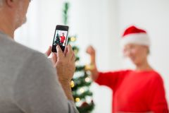 Close up of senior man picturing wife at christmas. Holidays and people concept - close up of senior men with smartphone photographing happy senior women Stock Photo