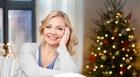 Middle aged woman over christmas tree at home stock photos