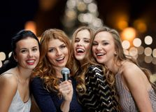 Women with microphone singing karaoke at christmas. Holidays and people concept - happy women with microphone singing karaoke at new year party over christmas Royalty Free Stock Photo