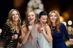 Women with microphone singing karaoke at christmas. Holidays and people concept - happy women with microphone singing karaoke at new year party over christmas Royalty Free Stock Image