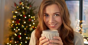 Happy woman with cup of tea or coffee on christmas stock photos