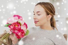Happy woman smelling flowers at home Stock Images