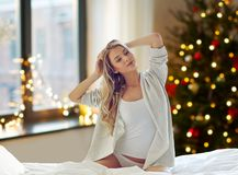 Young woman stretching in bed at home on christmas stock photography