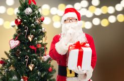 Santa claus with gift box at christmas tree. Holidays and people concept - man in costume of santa claus with gift box and christmas tree over lights background Stock Images