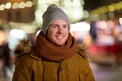 Happy young man over christmas lights in winter Stock Photo