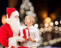 Santa claus and happy boy with christmas gift. Holidays and people concept - santa claus and happy little boy with gift box over christmas tree lights background Royalty Free Stock Image
