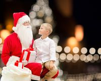 Santa claus and happy boy with christmas gift. Holidays and people concept - santa claus and happy little boy with gift box over christmas tree lights background Royalty Free Stock Photos
