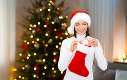 Woman putting christmas gift box into stocking royalty free stock photo