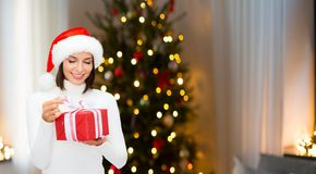 Smiling woman in santa hat with christmas gift stock image