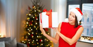 Smiling woman in santa hat with christmas gift stock photos