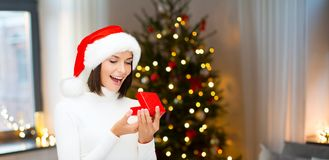 Surprised woman in santa hat with christmas gift stock images