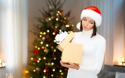 Smiling woman in santa hat with christmas gift stock photography