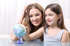 Holidays plan. Mother and daughter planning holidays with globe Stock Photography