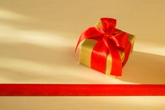 Small golden box with gift tied red bow. Holidays, present concept. Small golden box with gift tied decorative bow and red ribbon frame Stock Images