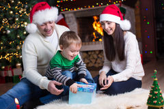 Holidays, presents, christmas concept - happy mother, father and child boy with gift box. Holidays, presents, christmas concept - happy family - mother, father Royalty Free Stock Photography