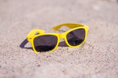 holidays, relax, travel and vacantion concept - yellow Sunglasses on sandy beach in summer royalty free stock photography