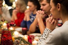 Close up of friends praying at christmas dinner. Holidays and religious concept - close up of friends having christmas dinner and praying before meal stock images
