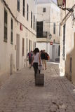 Holidays rental users walking downtown ciutadella in minorca vertical. Tourists carrying their luggages walk in a street downtown Ciutadella, on the island of Stock Photography