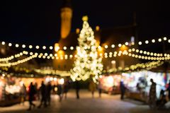 Christmas market at tallinn old town hall square. Holidays, sale and retail concept - evening christmas market at old town hall square in tallinn bokeh Stock Photos