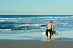 Papamoa Beach, Papamoa, New Zealand, July 07, 2019: an unidentified surfer preparing to enter the sea. Holidays at the sea; winter time in New Zealand; surfing stock images