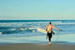 Papamoa Beach, Papamoa, New Zealand, July 07, 2019: an unidentified surfer preparing to enter the sea. Holidays at the sea; winter time in New Zealand; surfing royalty free stock photo