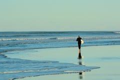 Papamoa Beach, Papamoa, New Zealand, July 07, 2019: an unidentified surfer preparing to enter the sea. Holidays at the sea; winter time in New Zealand; surfing royalty free stock image