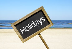 Holidays sign on a beach Stock Image
