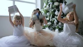Holidays, small girls throw gift boxes into air and smily in chic dresses near xmas tree with white ornaments